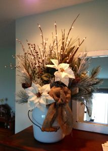 This faux floral arrangement features white poinsettias, lit branches, snow-covered evergreens, silver & maroon berries and a burlap bow placed in an antique enamel ware bucket
