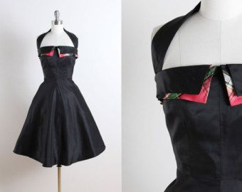 Vintage 1950s dress * Black sheer chiffon with flocked flowers and glitter  * Acetate and tulle lining  * Attached belt buckles in back  * Metal back zipper    Condition   In excellent vintage condition. Size   Fits like modern size XS/S.    Accessories not included.    Some clothes may be clipped on dress form to show best fit for appropriate size.    Length 43  Waist to Bottom Hem 28  Bodice Length 15  Bust 38  Shoulders Sleeves Waist 26  Hips Bodice Allowance 1  Hem Allowance More…