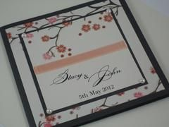 A very stylish 140 sq fold wedding invitation displaying a classic 3D Cherry Blossom design spread over two layers of Quartz Card with a contrast of Onyx, Peach Ribbon & Pearls.  This wonderful wedding invitation can be printed on a selected range of cards and modified to suite your color theme or individual events (whether it be a wedding, engagement or any other special occasion)