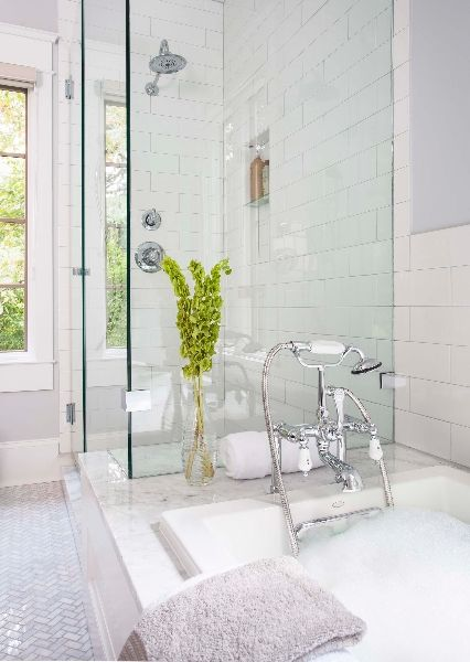 Master bathroom features drop-in bathtub attached to shower accented with subway tile shower surround and niche over marble herringbone floor.