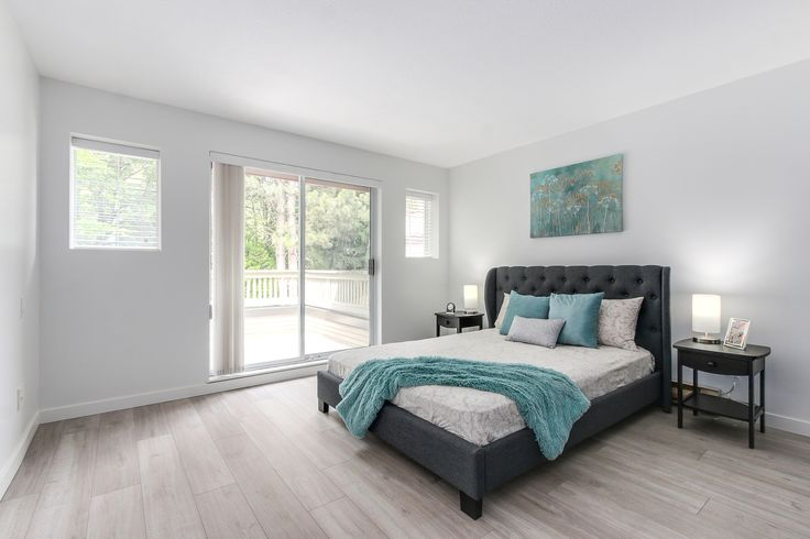 Spacious bright bedroom with teal colour accessories