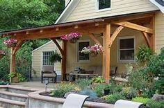 tin roof covered decks - this looks too rustic with so much wood showing - wood need to trim out and paint, and stone on pillars