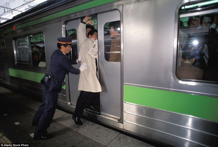 The rush hour conditions leave absolutely no room for dignity. Pictured is a well-dressed businessman being unceremoniously shoved in