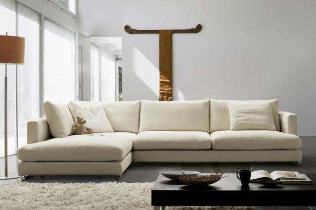 Divano angolare dalle tonalità chiare - Divano ad angolo bianco panna dallo stile classico.