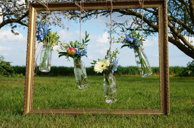 Mini milk bottles hanging in a picture frame with flowers. Flowers by Davina