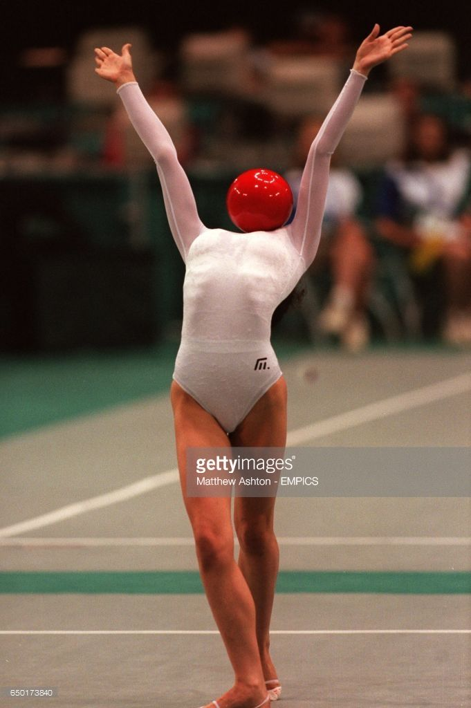Maria Petrova, Bulgaria balances the red ball on her chest.