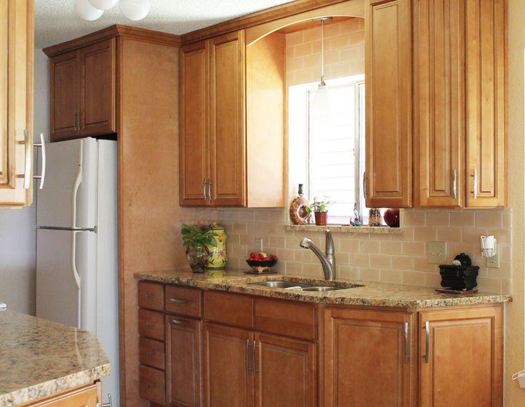 Warm #kitchen design with granite countertops, peach subway #tile