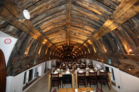 """The restaurant """"Mallemukken"""" is located in """"De Røde Barakker"""", only 300 m from the North Sea, next to the channel of Thyborøn.   The setting is a cutter turned upside down and with an interesting maritime interior. Here you can enjoy the special atmosphere and be tempted by a """"sailor's buffet"""" consisting of a wide range of fish and meat dishes."""