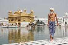 Um peregrino siquista com o Harmandir Sahib (Templo Dourado) em Amritsar, ao fundo.