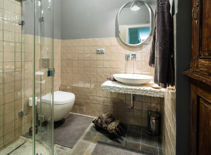 Elegant bathroom features handmade glazed ceramic tiles and glass shower.