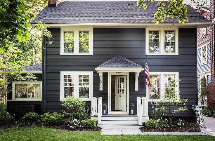 A sleek charcoal gray and crisp white painted clapboard facade make this charming Michigan home feel modern.