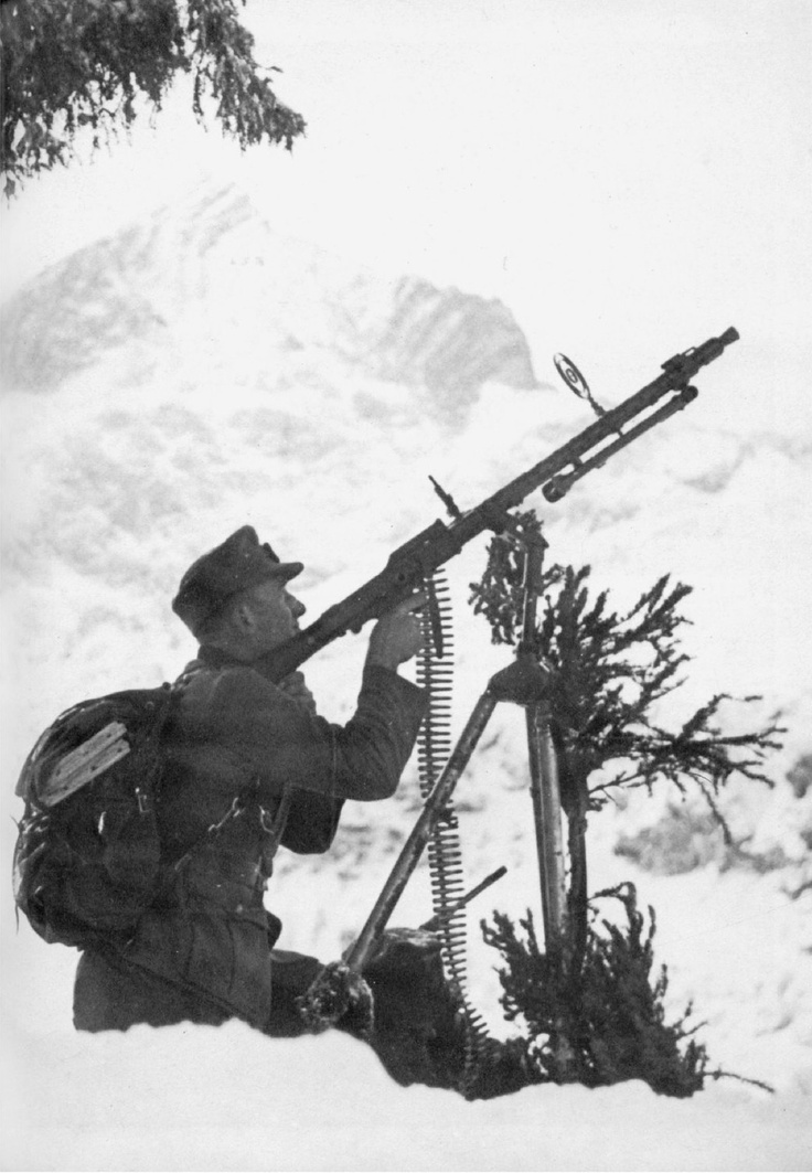 A soldier from a Mountain Infantry Regiment (Gebirgsjäger) aims his MG-34 mounted on a tripod for use against aircraft. A full 360 degree traverse was possible with the tripod mount. Note the anti-aircraft spider sight, used in conjunction with the rear sights.