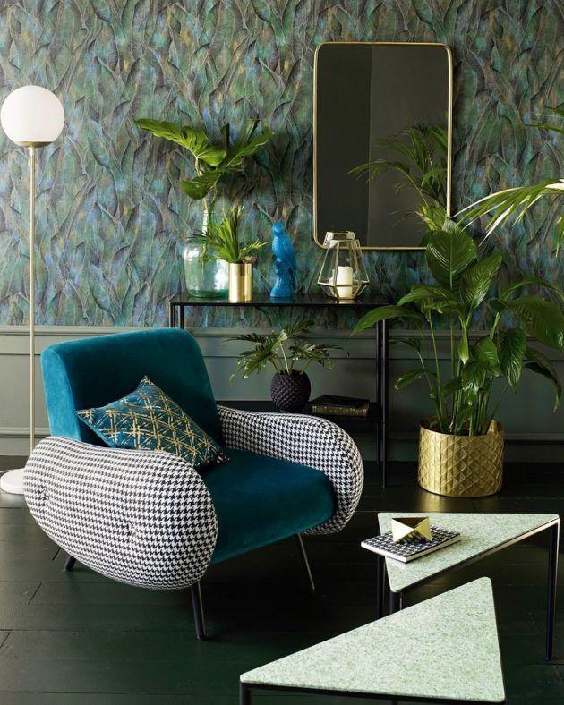 Pour une ambiance années 50 60 la décoration du salon a associé fauteuil en velours et tissu pied de poule avec un lampadaire en laiton et marbre ainsi qu'une table basse triangle en granito et terrazzo.