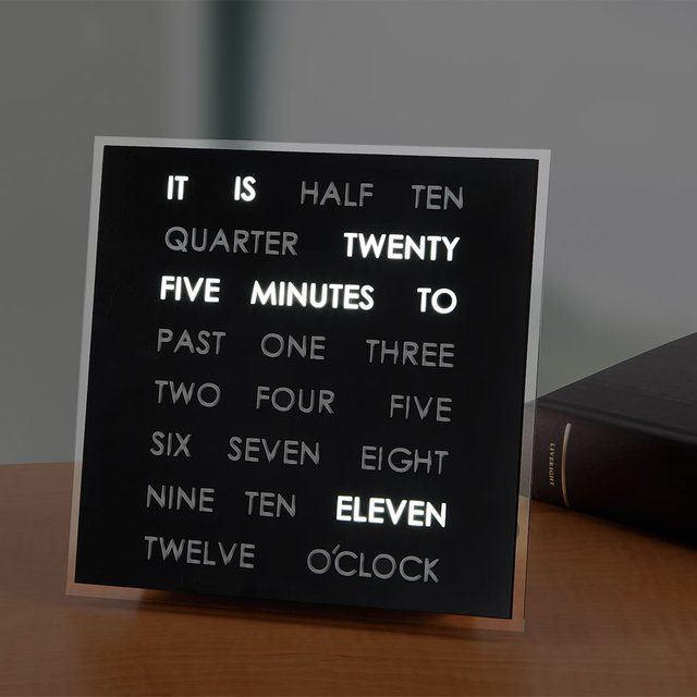 """The Reading Time Clock displays the time as a complete sentence. The clock uses only 23 words to convey the time in five-minute increments. It uses 3/4""""-high capital letters backlit by a bright LED to tell the time—10:55 is shown as """"It Is Five Minutes To Eleven"""" whereas 3:15 displays as """"It Is Quarter Past Three."""" It can mount to a wall or stand up on a desk. Includes AC adapter. 7 3/4"""" sq. x 1 3/4"""" D. (1 lb.) Please allow 2 weeks for shipping."""