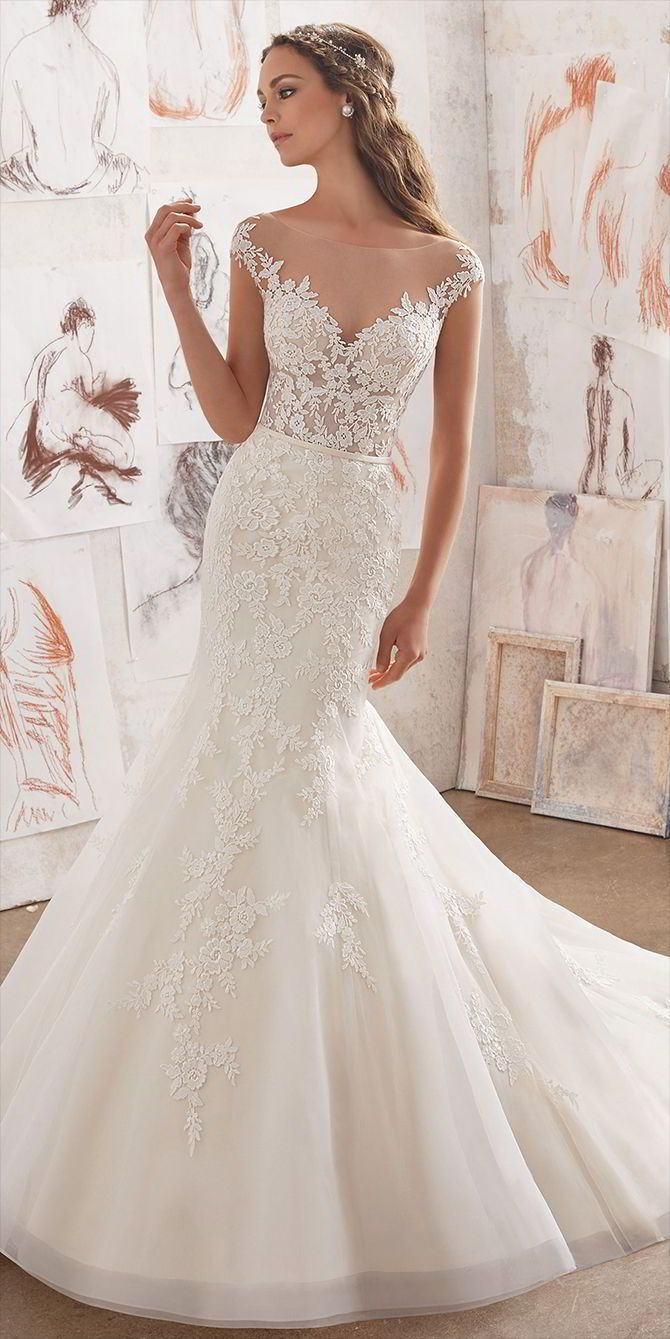 Gorgeous Fit & Flare Wedding Dress Featuring a Beautifully Embellished Bodice Adorned with Venice Lace Appliques on Net. An Off-the-Shoulder Illusion Neckline and Cap Sleeves Complete the Ultra Feminine Look. Matching Satin Lining Included.
