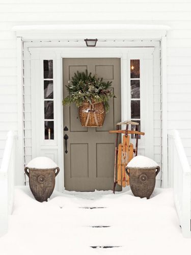 Antique collectibles charms the front door of this Connecticut home. Tuck greenery and berries inside a trapper's basket for a fresh alternative to the classic wreath.