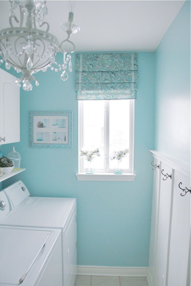 The aqua wall, shade, and chandelier turn  this tiny laundry room into THE PLACE TO HANG OUT! (Love the vintage-looking clothes hooks and the little bird cage and nest on the shelf.) Nicely done!