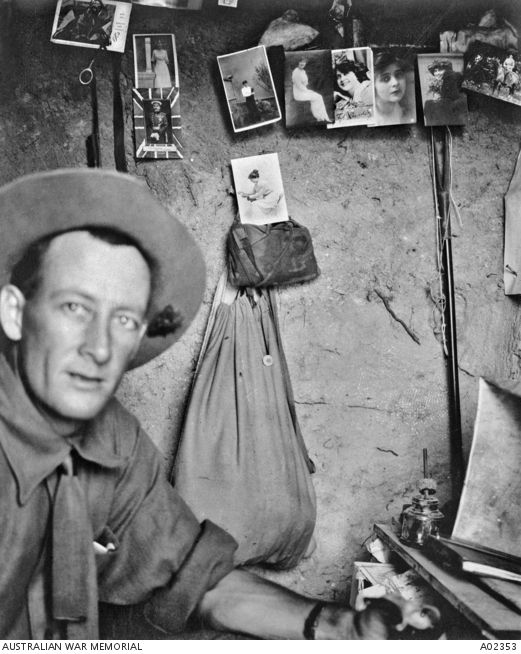 Ottoman Empire: Turkey, Marmara, Chanak, Gallipoli Peninsula. 1915. Lieutenant Oliver Hogue in his dugout at Anzac. Several portraits of a woman and one of Lord Kitchener are hanging on the wall. A bag hanging from the wall might contain an early gas mask. Hogue, a journalist, wrote several books under the penname 'Trooper Bluegum'. He died of influenza in England on 3 March 1919.
