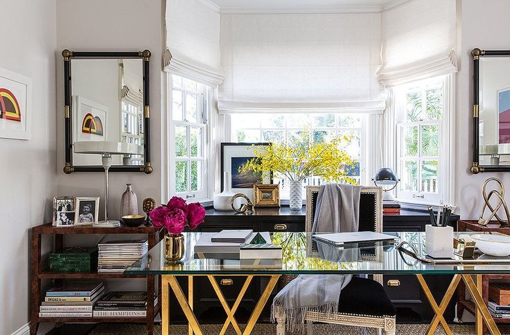 A healthy mix of style periods: The French traditionalism of a Louis XV-style chair, with whitewashed trim, sets off the modern lines of the glass desk. On each wall hangsa colorful mod artwork.