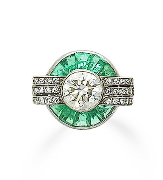 An art deco emerald and diamond dress ring, circa 1935  Of odeonesque design, set to the centre with a brilliant-cut diamond, within a radiating surround of tapered baguette-cut emeralds and single-cut diamonds, principal diamond approximately 2.50 carats, ring size L