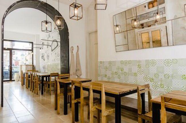I due locali destinati al ristorante sono comunicanti ma separati da un'apertura ad arco, vincolo di un muro portante originale. Il pavimento è rivestito di pietra di Cave Tinella, largamente usata nell'architettura pugliese. Le lampade in metallo sono realizzate artigianalmente da Bernardo Palazzo (foto di Gregory Abbate)