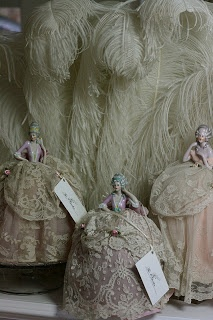 These little porcelain ladies with their  wonderful antique lace gowns would  grace the dressing tables of wealthy  ladies, they could stick their hatpins  and brooches in the padded skirt and  drape their necklaces around them.