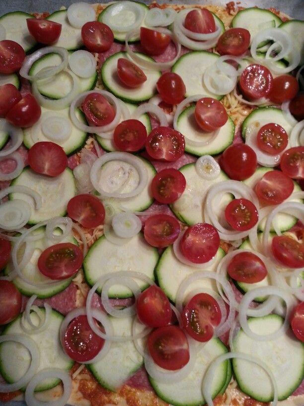 Homemade plate pizza: pesto rosso, cheese, salami, zucchini, onion and tomato