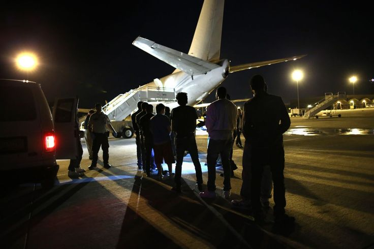 Undocumented immigrants wait to be loaded onto an Immigration and Customs Enforcement (ICE), charter jet early on October 15, 2015 in Mesa, Arizona.