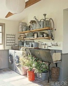 """The vintage industrial ambiance of this laundry room from Elle Décor tops my list!  I just love how the garden room and laundry room can live together so harmoniously.  The deep trough-like sink, vintage bottle drying racks (perfect for drying intimates – genius!), and the fantastic collection of galvanized watering cans make me swoon."""