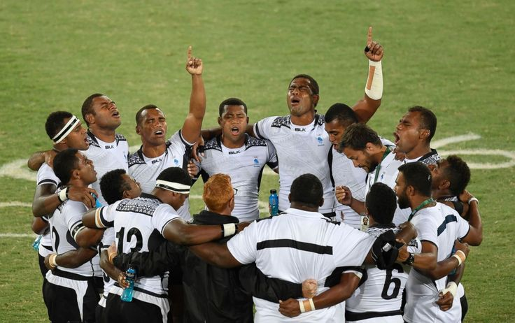 Fiji's players pray after winning the mens rugby sevens gold medal match between…