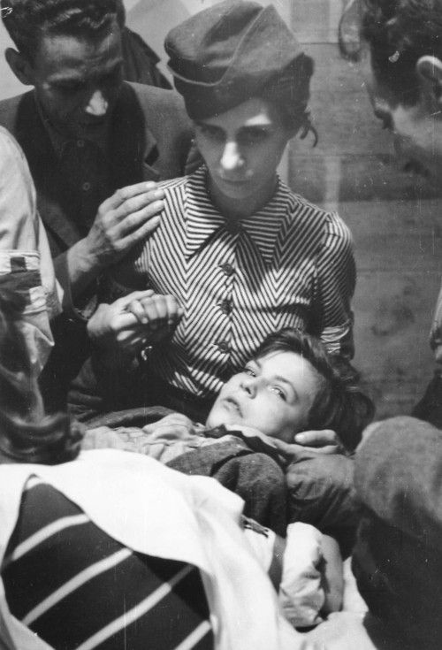 Poland, 1944: Nurse comforts a wounded boy in a field hospital during the Warsaw Uprising