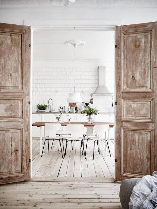 ruwe plankenvloer en witte tegels aan de keukenmuur. Oude deuren
