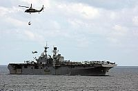 170121-N-FM530-024 ATLANTIC OCEAN (Jan. 21, 2017) MH-60S Sea Hawk helicopters deliver supplies to the amphibious assault ship USS Bataan (LHD 5) during a vertical replenishment. Bataan is underway conducting Composite Training Unit Exercise with its Amphibious Ready Group in preparation for an upcoming deployment. (U.S. Navy photo by Mass Communication Specialist 2nd Class Brent Pyfrom/Released)