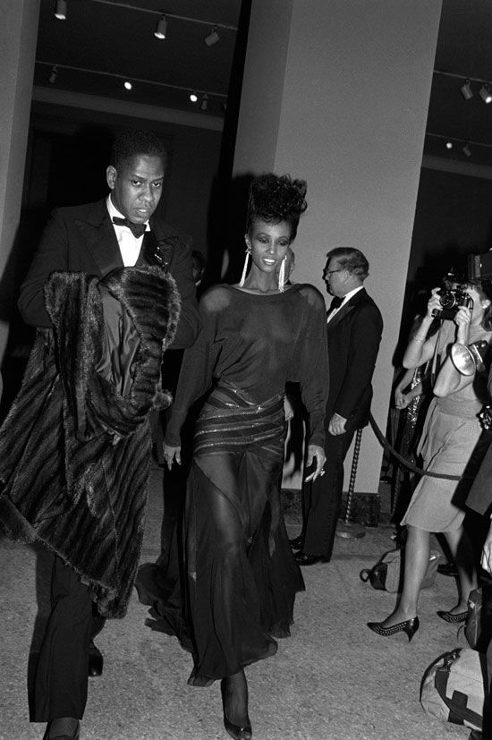 Fashion editor Andre Leon Talley and supermodel Iman arriving at the opening of the Metropolitan Museum of Art's exhibition on YSL. (December 1983)