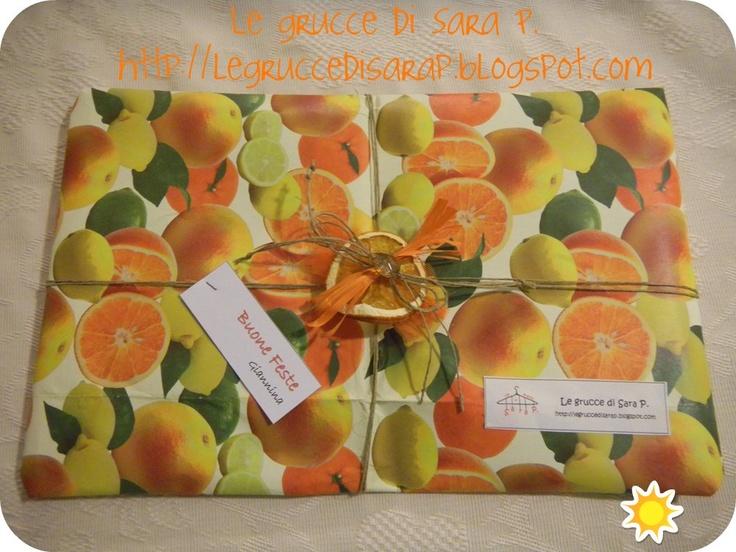 Pacco regalo con stampe di agrumi e una fetta di arancia essiccata