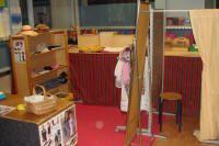 een kledingwinkel: Een kassa, een passpiegel, kleding op hangertjes (zomer en winter, groot en klein) schoenendozen met schoenen, verschillende plastic tasjes van kledingwinkels, een mandje op de toonbank met armbanden en kettingen.