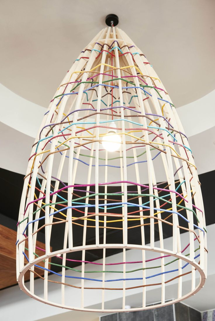 """When you think """"ekhaya"""" what comes to mind? Lighting! That's our answer. Bespoke cage light made by Jacques Cronje float above a seating area. The timber fins are interwoven with colorful leather """"riempie"""" laces. Nando's Rustenburg"""