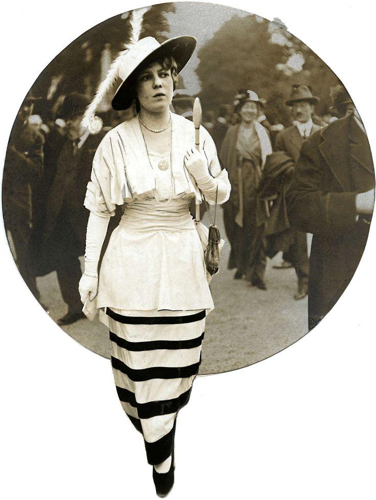Damesmode. Op de renbaan van Longchamps laten modellen de laatste mode zien. Een  lange  gestreepte rok en een jakje met gerimpelde taille en een  kort jasje in dezelfde stof daaroverheen. Een hoed met brede rand en en een veer wordt erbij gedragen. Longchamps,Frankrijk, 1914.