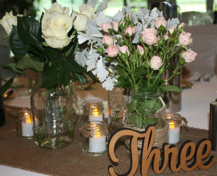 Jars with varying floral arrangements on a hessian runner.