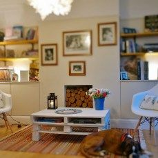 cosy sitting room displaying a palette coffee table surrounded by two Eames chairs