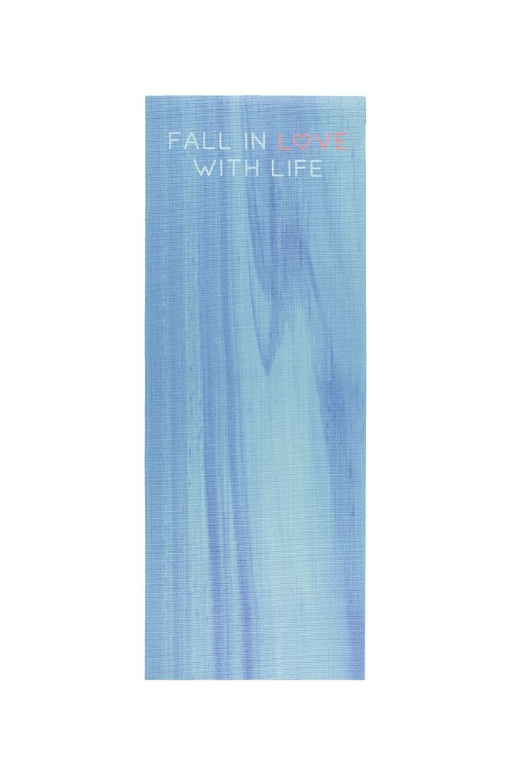 "A yoga mat featuring a textured cushion surface, tie-dye pattern, and a ""Fall In Love With Life"" graphic on the front."
