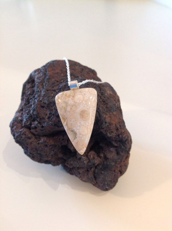 A fossilised coral agate cabochon in cream and taupe tones clearly detailing fossilised coral structures. The stone is 33mm long by 22mm wide at its widest point. It is mounted on a sterling silver bail and hung on a 18 Sterling silver rope chain. It is presented in black box with a