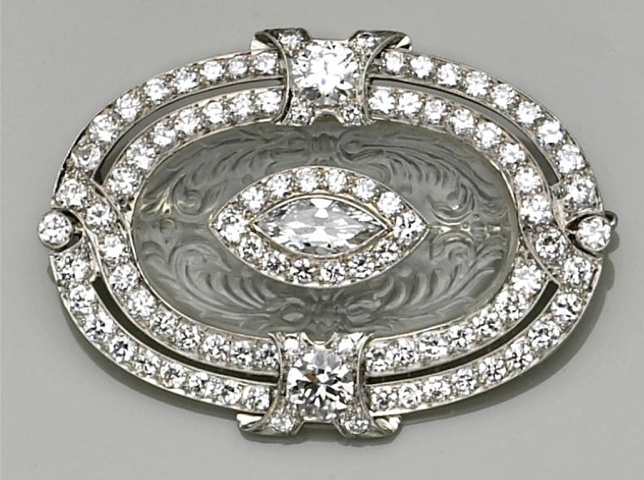 Art Deco. Rock crystal, diamond & platinum brooch, ca 1920, centering a marquise & old European-cut diamond cluster within a carved rock crystal oval panel & further two-row old European-cut diamond frame; est total diamond weight: 6.50 cts.