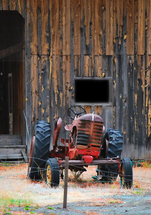 Old tractor sits quietly in front of an old barn
