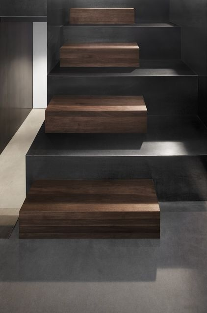 The staircase mixes walnut and steel. The contrast of espresso and ebony tones is gorgeous, with the steps looking like art installations.