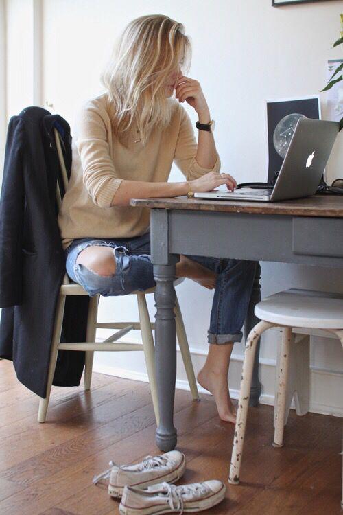 mujer sentada en un escritorio frente a una computadora pensando