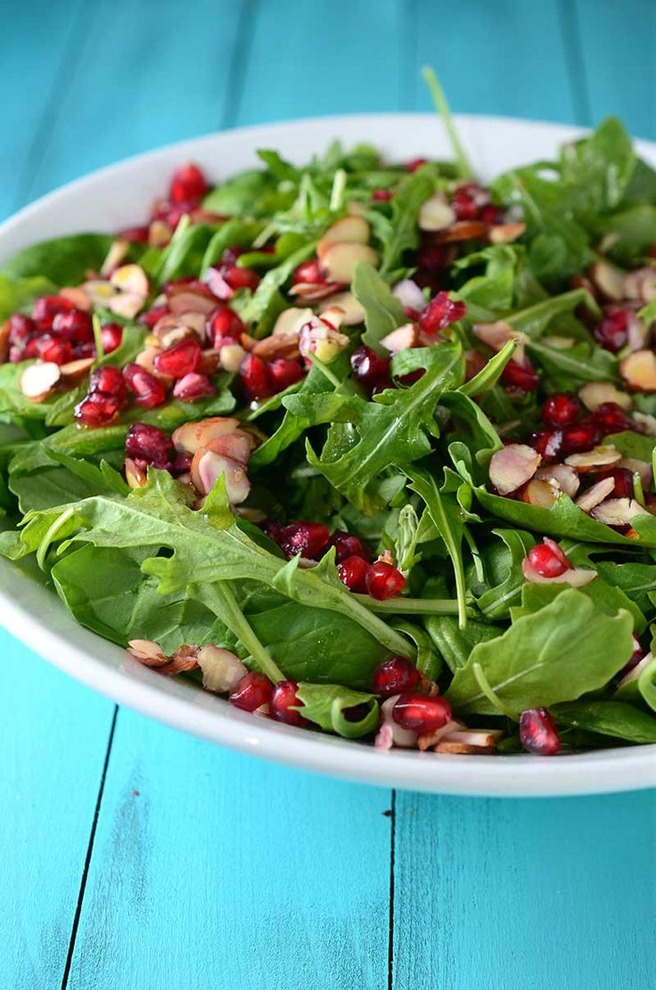 Spinach, Arugula, Almond and Pomegranate Salad tossed in a Lemon-Garlic Vinaigrette. Perfect for Thanksgiving!