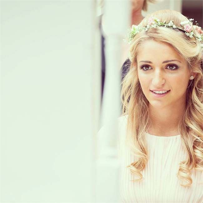 Half up half down hairstyle with wedding flowers