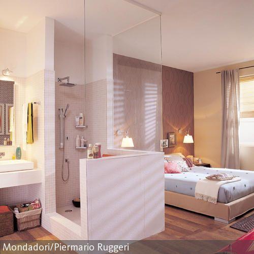In diesem Schlafzimmer mit integriertem Bad fungiert die Dusche als Raumtrenner. Durch die Verglasung wirkt der Raum hell und einladend.
