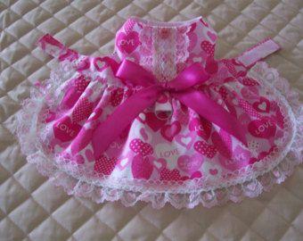 C'est un facile sur - robe avec fermeture velcro devant du cou et du ventre. La robe est faite de coton avec un design de coeurs et d'amour. La robe a une jupe froncée bordée de blanc et coeurs rose dentelle et le corsage a 2 rangées de la même dentelle. Complet avec un noeud en satin assorti et bouton coeur D-ring. La robe est entièrement doublée donc aucuns coutures ne sont exposés. Une robe spéciale de la Saint-Valentin pour votre fille poilue.  Cette robe est adaptée pour un petit chien…